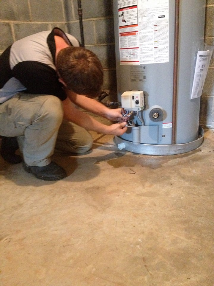 image of a technician working on a water heater