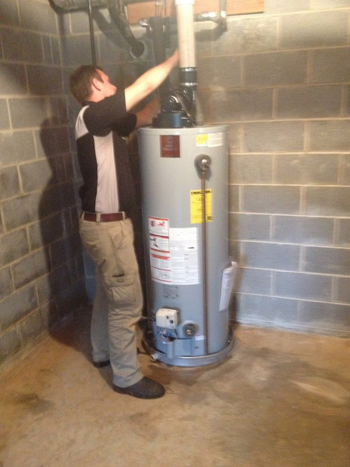 image of a technician checking a water heater connections
