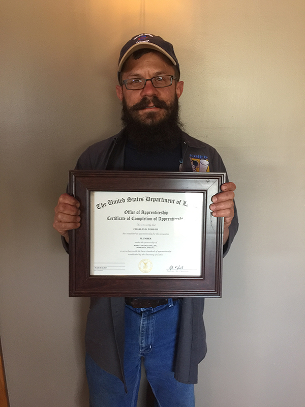 Employee Charles Todd holding a Certificate of Apprenticeship for his Plumbing License