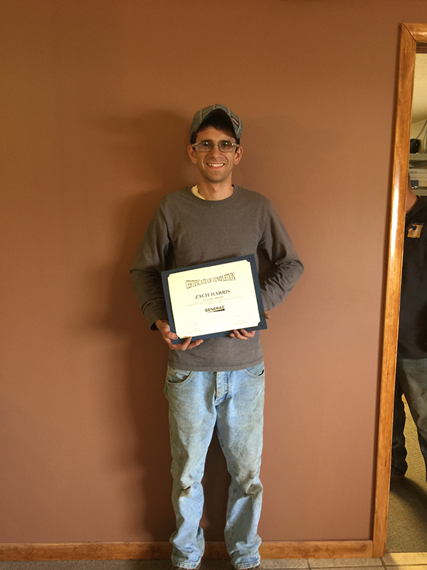 Employee Zach Harris holding a Certificate of Completion for Generac Generator Installations