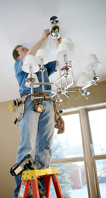 Master Electrician changing light fixture while standing on a ladder