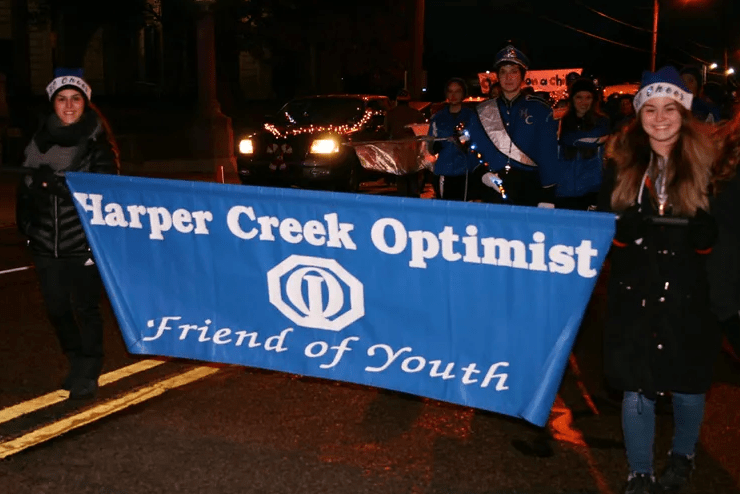 Harper Creek Optimist members holding flag