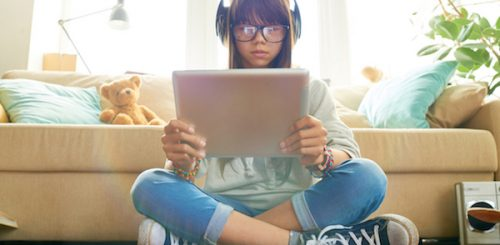 Teenage girl holding digital tablet and looking at screen