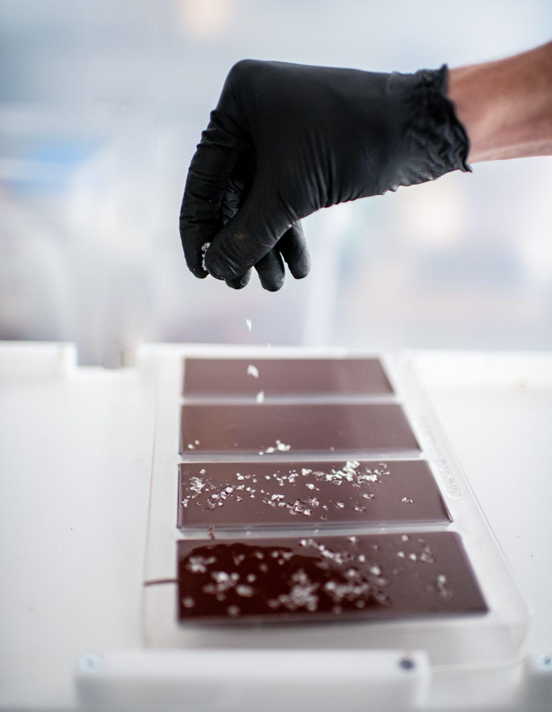Sprinkling salt into the backs of melted chocolate bars.