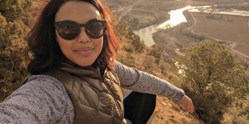 Reverend Aline Silva in sunglasses on a mountainside
