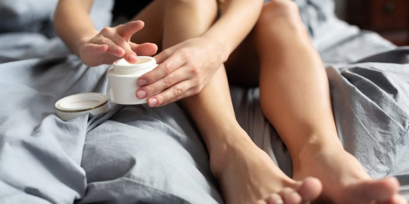 Woman applying cream to leg
