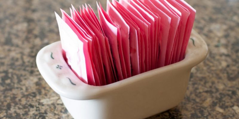 Pink artificial sweetener packets in ceramic dish