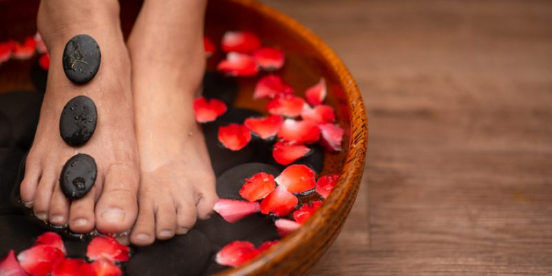 Beautiful female feet at spa soaking for foot care