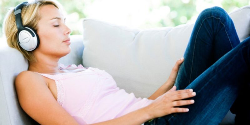Woman relaxing on couch listening to headphones
