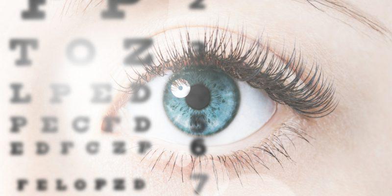 Close up image of blue human eye through eye chart