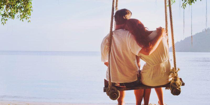 A couple swings on a beach