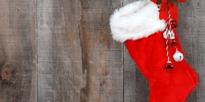 Christmas stocking hanging against gray backdrop