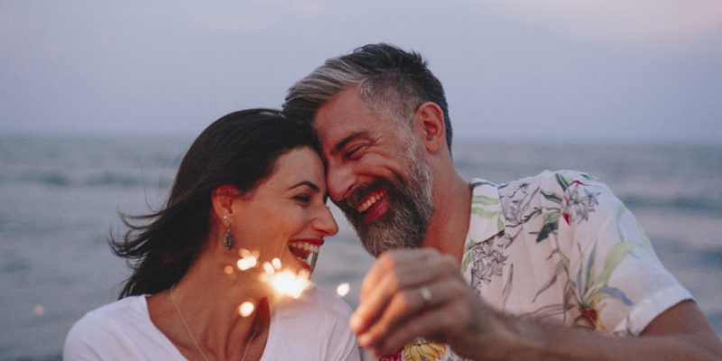 Mature couple playing with sparklers for Passion & Presence