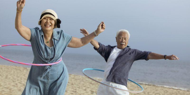 couple hula hooping on a beach
