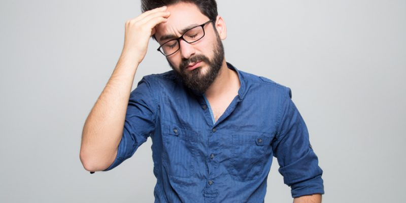A man touches his face with an exasperated expression