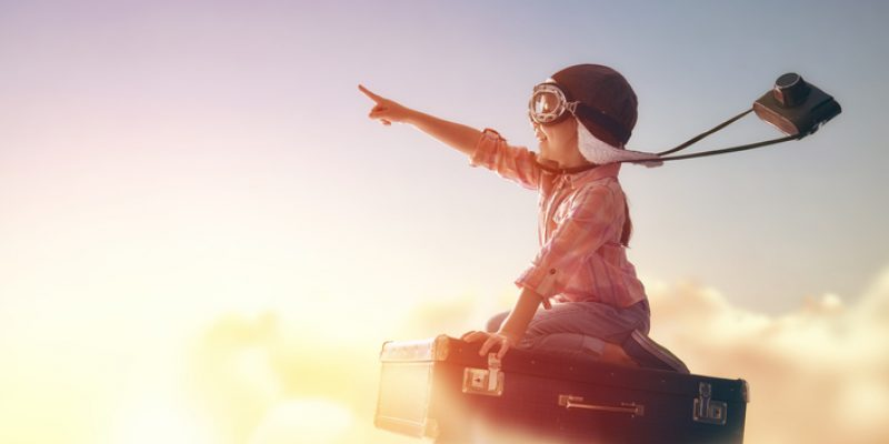 Child daydreams of flying through the air on a suitcase