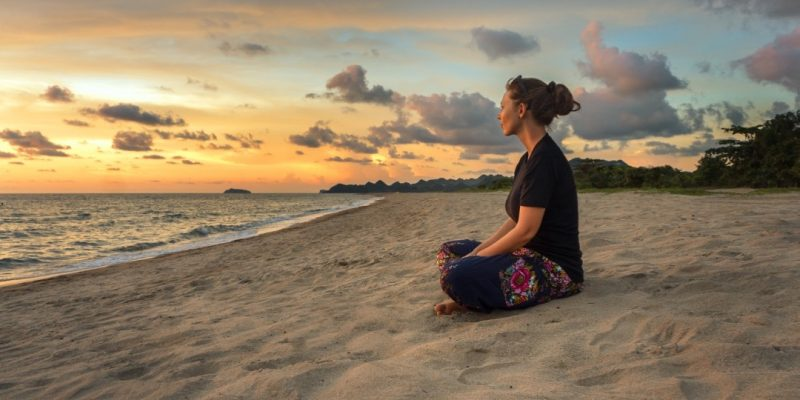 Woman sitting on beach at sunset