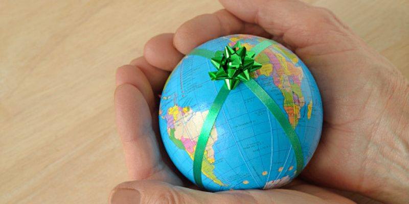 Woman hands holding a small earth with a green ribbon