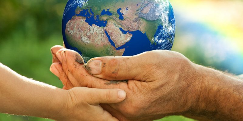 Elderly and child's hands holding the earth with a rainbow.