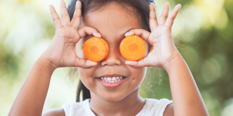 Cute little girl holds carrot rounds up to her eyes as a joke.