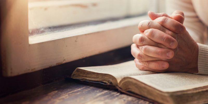 A woman praying by a window