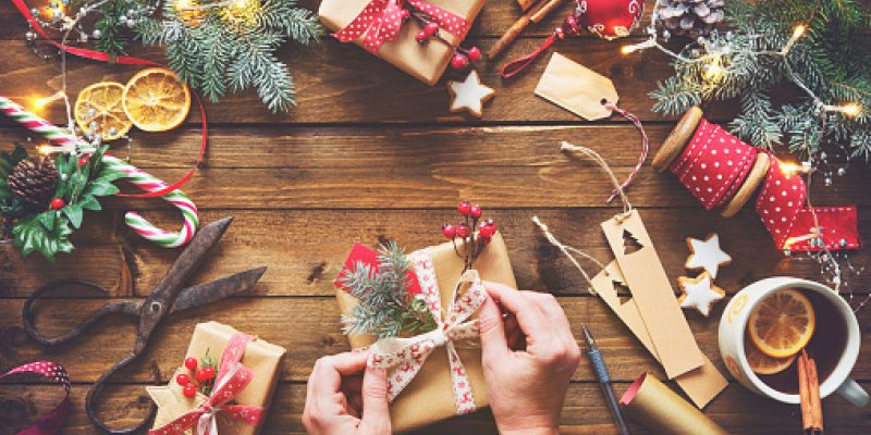 Top view of a woman's hands wrapping homemade Christmas holiday presents in craft paper with ribbon on wooden table