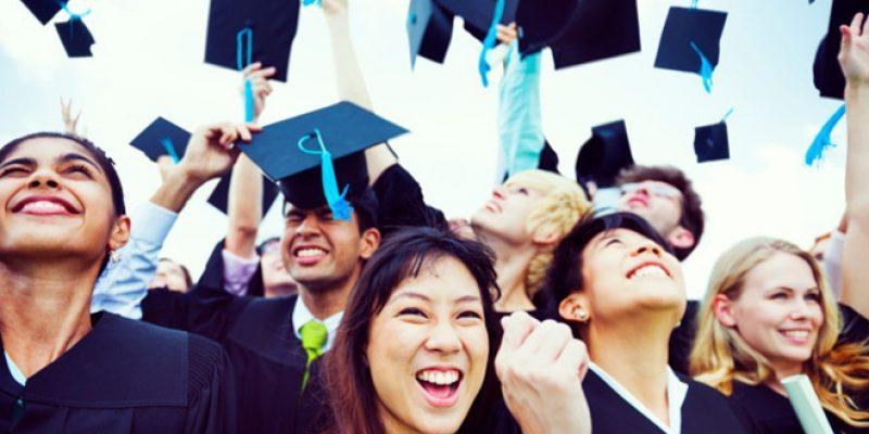 Happy graduates throwing caps in air