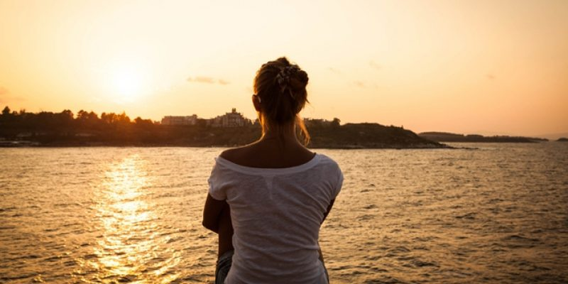 Woman staring at the water, as if coping with deep sadness
