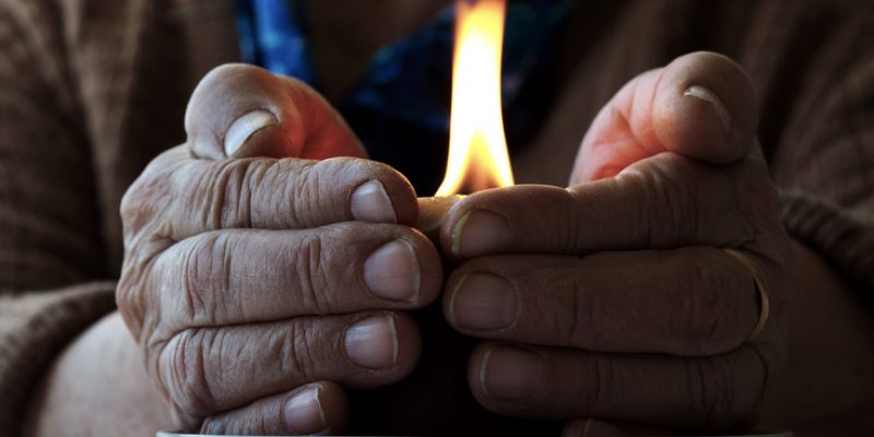 Devotional hands around a candle