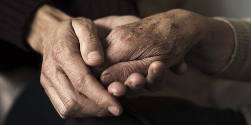 Holding hands with an elderly parent