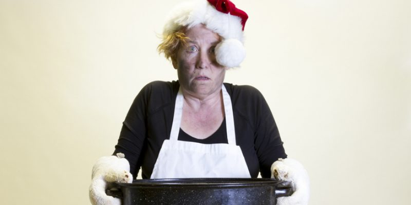 Woman with singed face holding roasting pan with Santa hat and apron.
