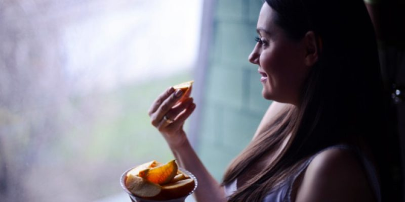 Woman eating orange in window