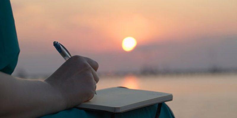 Woman journaling at sunset