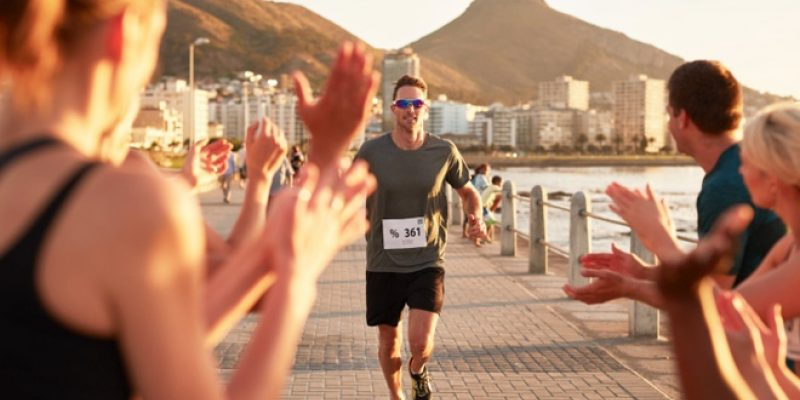 Man being cheered on while finishing race
