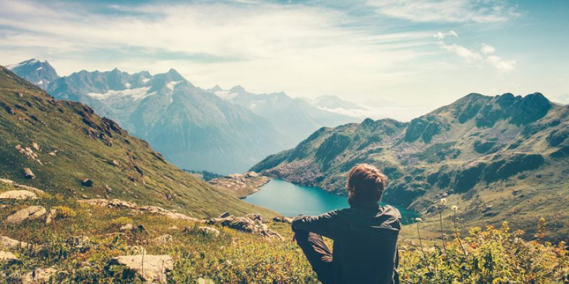 Man sitting on a mountain top looking at the view