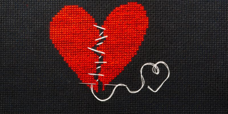 Forgiveness, represented by two halves of a heart embroidered being sewn back together with black thread.