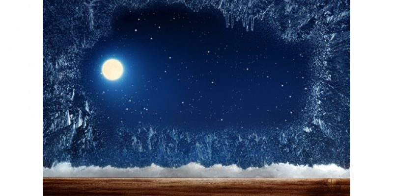 Moon outside of an icy winter window