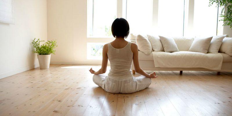 Woman meditating in light room