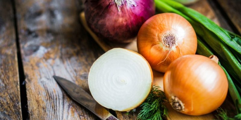 Colorful onions on wood surface