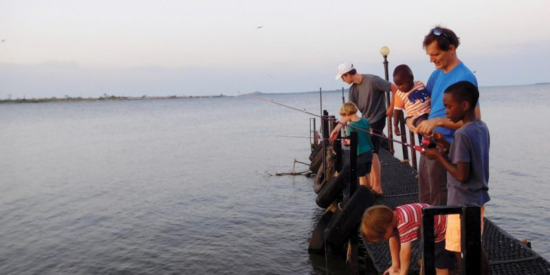 Paul Sutherland in Uganda fishing with some kids off a dock.