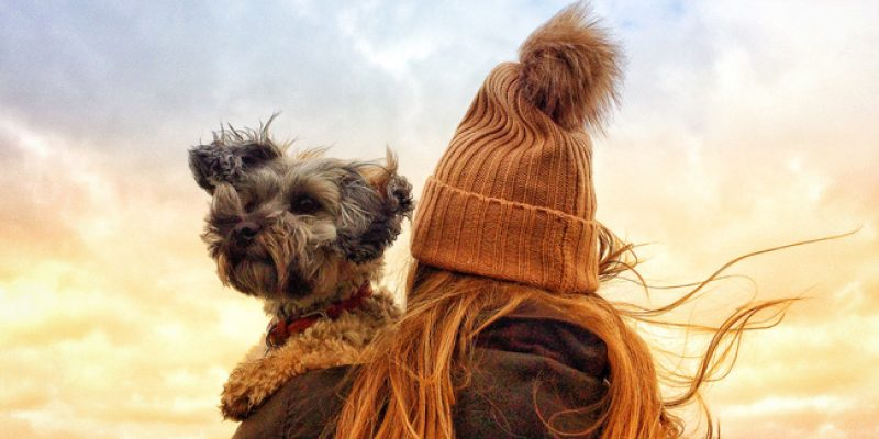 Woman in pompom hat and scarf holding dog over her shoulder
