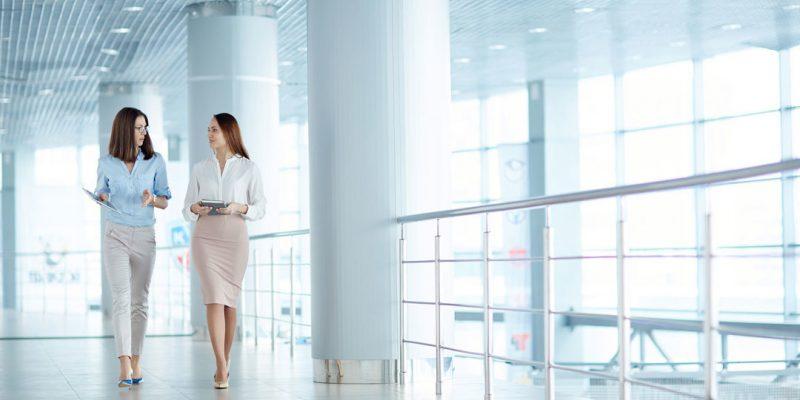 Two women walking while working