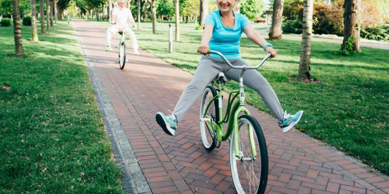 Happy senior couple riding their bikes in the park, playfully lifting their legs up as they ride