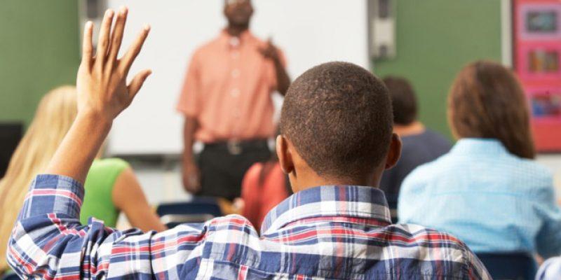 Man raises hand in class