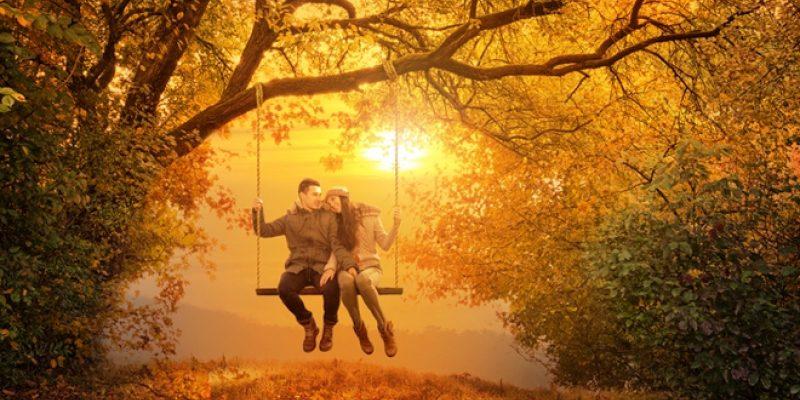 Couple swinging on swing in fall