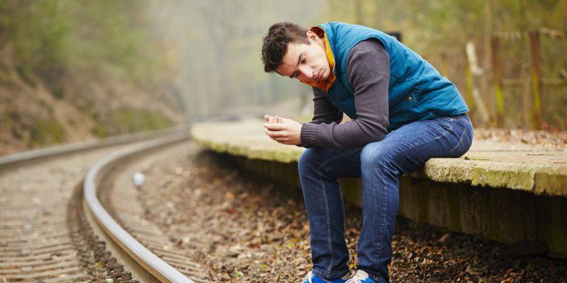 Boy sitting on train tracks