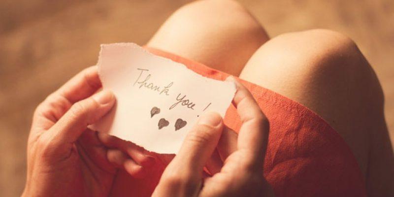 Woman holding gratitude note