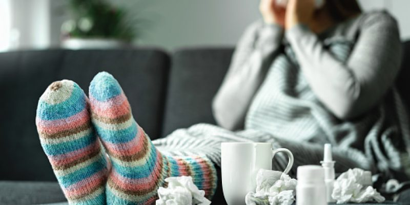 Sick woman with flu, cold, fever and cough sitting on couch at home wearing wool sock surrounding by tissue