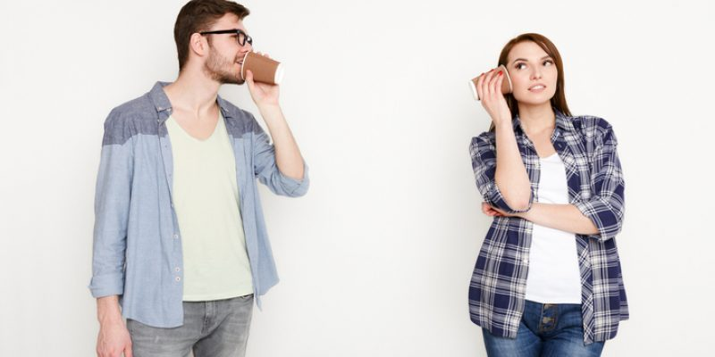 Young casual couple talking through tin can phone