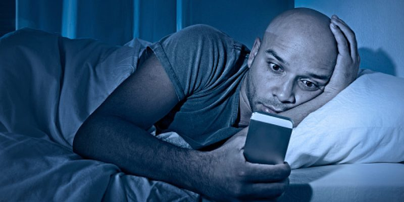 Man staring at smartphone in bed at night